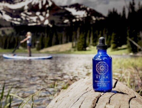 Woman on SUP at colorado mountain lake feeling balance calm spiritual with vadiance bottle in foreground